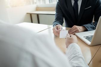 Giovane imprenditore all'incontro di assunzione in ufficio, incontro alla lobby di ufficio, cambiare biglietti da visita.