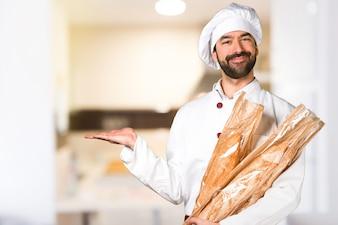 Giovane panettiere che tiene un po 'di pane e tiene qualcosa in cucina