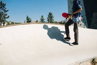 Giovane pattinatore che tiene il suo skateboard