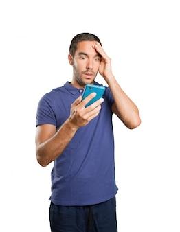 Giovane sorpreso utilizzando un telefono cellulare su sfondo bianco
