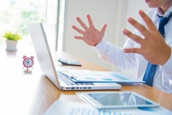 Giovane stressato bel uomo d'affari che lavora alla scrivania in ufficio moderno gridando allo schermo del computer portatile e arrabbiato circa la situazione finanziaria, geloso di capacità rivali, in grado di soddisfare le esigenze del cliente