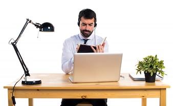 Giovane uomo che lavora con un libro di lettura auricolare