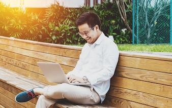 Giovane uomo d'affari felice che lavora al computer portatile a giardino