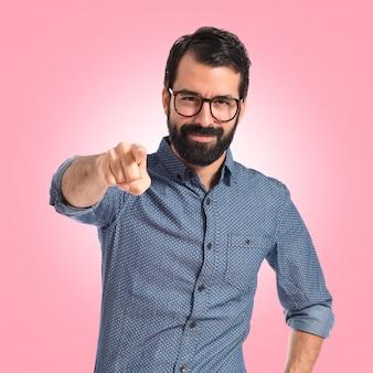 Giovane uomo di hipster che punta alla parte anteriore sullo sfondo colorato