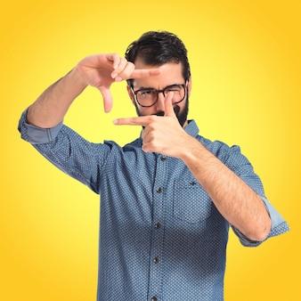 Giovane uomo di hipster messa a fuoco con le dita sullo sfondo colorato