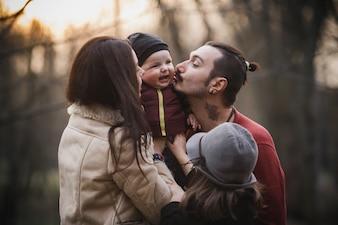 Giovani genitori baciare il bambino mentre presentano