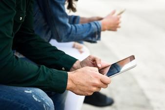 Giovani persone irriconoscibili che utilizzano smartphone e tablet computer