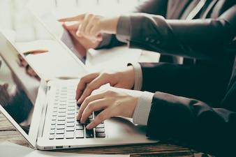 Gli uomini d'affari con un computer portatile e un tablet