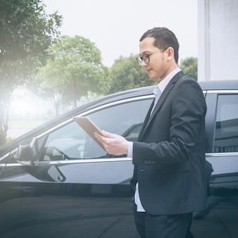 Gli uomini d'affari lavorano con i computer portatili sul lato dell'auto