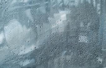 Gocce d'acqua sul vetro della finestra per lo sfondo.