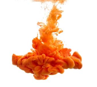 Goccia di vernice arancione che cade in acqua