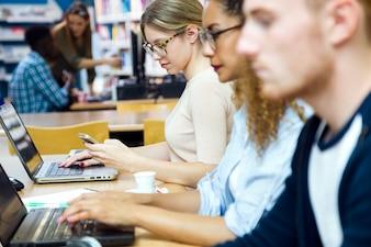 Gruppo di amici che studiano in una biblioteca universitaria.