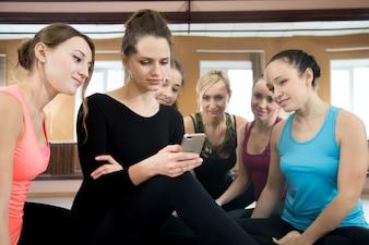 Gruppo di belle ragazze sportive che usano il telefono cellulare sulla pausa nella palestra di sport