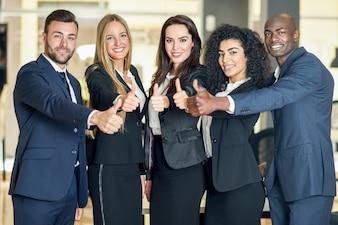 Gruppo di imprenditori con il pollice gesto in ufficio moderno. Persone multietniche che lavorano insieme. Concetto di lavoro di squadra.