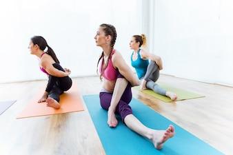 Gruppo di persone che praticano yoga a casa. Marichyasana posa.