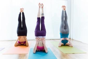 Gruppo di persone che praticano yoga a casa. Sarvangasana posa.