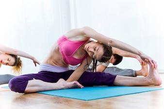 Gruppo di persone che praticano yoga a casa.