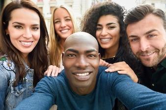 Gruppo multirazziale di giovani che prendono selfie