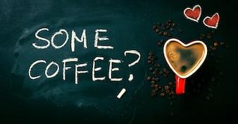 Gustosi caffè espresso in una forma di cuore tazza rossa su una lavagna.