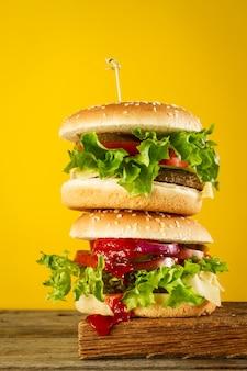 Gustosi hamburger malsani su tavola di legno, pronti a mangiare o servire.