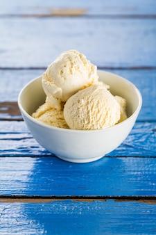 Gustoso ghiaccio di vaniglia scopa in ciotola sul tavolo rustico in legno blu. Avvicinamento.