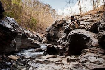 Guy seduto al fiume selvaggio
