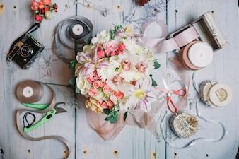 Il bouquet di nozze si trova tra nastri, telecamere e forbici sul t
