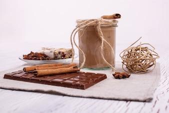 Il coctail marrone detox con bastoncini di cannella e cioccolato si trovano sul tavolo
