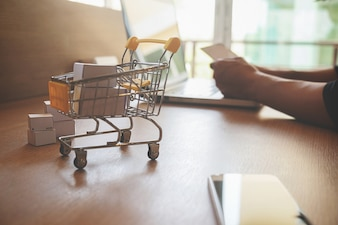 Internet concetto di shopping online con il computer portatile e shopping cart.Vintage tono retro effetto filtro, soft focus (attenzione selettiva)