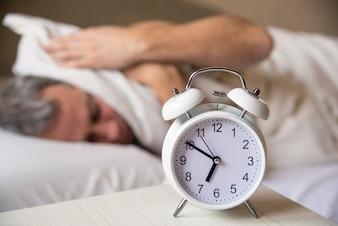 L'uomo addormentato disturbato dalla sveglia mattutina. Sei sonnolento