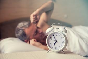 L'uomo addormentato disturbato dalla sveglia mattutina. Uomo arrabbiato a letto risvegliato da un rumore. Svegliato. L'uomo che giaceva a letto spegne una sveglia la mattina alle 7 del mattino