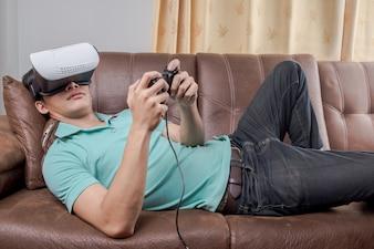 L'uomo che indossa occhiali di realtà virtuale guardando film o giocando videogiochi. Il design della cuffia auricolare è generico e nessun logo.
