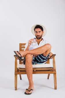L'uomo in estate indossa sulla sedia con un bicchiere d'acqua
