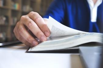 L'uomo legge un libro. L'istruzione, l'accademico, l'apprendimento e l'esame concetto.