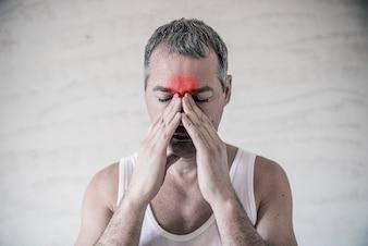 L'uomo tiene la zona del naso e del seno con le dita in un dolore ovvio da un mal di testa nella parte anteriore della fronte. Dolore sinusale