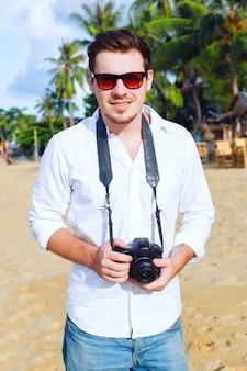L'uomo con la camicia bianca che tiene la sua macchina fotografica in una giornata in spiaggia