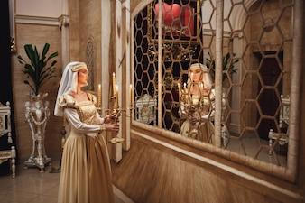 La principessa in abiti dorati porta candelabro con candele accese