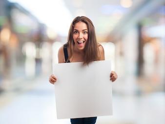 La ragazza felice in possesso di un cartello bianco con sfondo sfocato