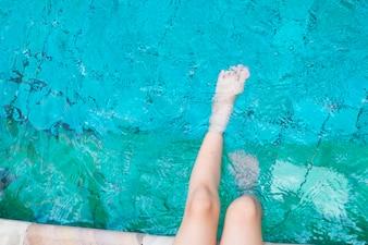 La ragazza rilassante piedi con acqua in piscina.