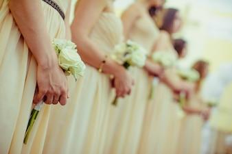 Le amiche della sposa di un matrimonio con i fiori in mano