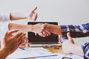 Le persone d'affari si stringono la mano, finendo una riunione