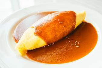 Le uova di omelette avvolgono il riso con la salsa
