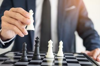 Leader di affari di un business di successo che tiene lo scacchi in mano Composito digitale di pezzi di scacchi