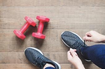 Legare scarpe sportive, donna asiatica preparandosi per il trainning di peso. Esercizio, formazione fisica. Concetto di stile di vita sano