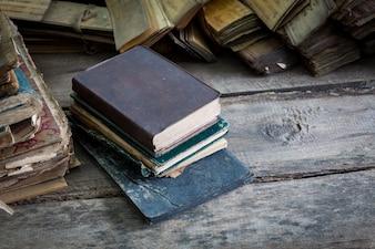 Libri accatastati su un pavimento di legno