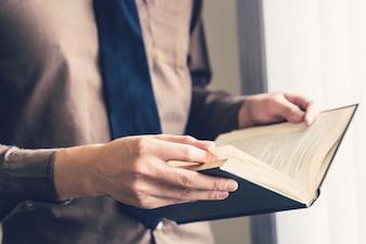 Libro di lettura della mano dell'uomo di affari e lettura alla finestra.
