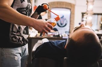 Lo sposo seduto sulla sedia in negozio di barbiere
