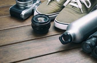 Macchina fotografica, lente, binocolo, scarpe di tela, bottiglia sportiva sul retro tavolo di legno