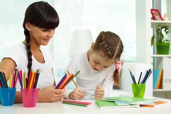Madre aiutare sua figlia a disegnare