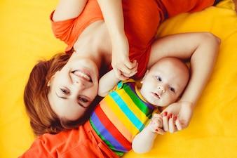 Madre e suo figlio sdraiata su un letto di colore giallo